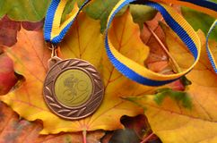 Lviv/Ukraine - October 7 2018: Medal from autumn Kid`s bicycle race in Lviv. Yellow maple leaves us a background. Medal for participation stock photo
