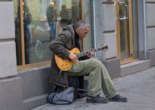 Lviv, Ukraine - October 18, 2015: Street musician playing an electric guitar. Near a store window Stock Photo