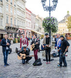 Lviv, Ukraine - September 2015: Band of guys playing guitars and singing in the Market Square in the street in Lviv Royalty Free Stock Image