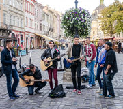 Lviv, Ukraine - September 2015: Band of guys playing guitars and singing in the Market Square in the street in Lviv Royalty Free Stock Images