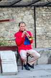 Lviv, Ukraine - September 2015: A lone trumpeter musician plays the trumpet sitting on a chair on the street of Lviv Stock Image