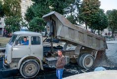 Lviv, Ukraine - September 2015: Truck unloads gravel road reconstruction on Liberty Avenue in Lviv Royalty Free Stock Images