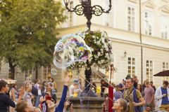 Man inflates big soap bubbles on Market Square. Wiev of city life Stock Photos