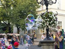 Man inflates big soap bubbles on Market Square. Wiev of city life Stock Photography