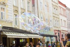 Man inflates big soap bubbles on Market Square. Wiev of city life stock image