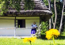 Old wooden house with old woman in flowered ethnic dress stock photo