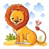 Löwe, der auf einer sandigen Wiese sitzt Stockbilder