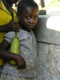 Lwizi, Katanga, Democratic Republic of the Congo, June 6th 2006: Girl stands holding fruit royalty free stock image