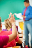 Lycée : La fille soulève la main dans la classe Images libres de droits