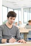 Lycée - le jeune étudiant mâle écrivent des notes images stock
