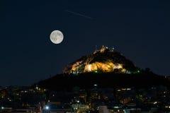 Lycabettus-Berg in Athen Griechenland gegen den Vollmond Augustes und eine Sternschnuppe lizenzfreie stockfotografie