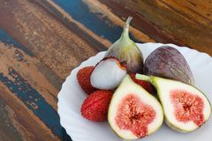 Lychee and figs on a wooden table Royalty Free Stock Photography