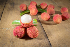 Lychee. Fresh lychees. Lychee with leaves on a wooden table Stock Photo
