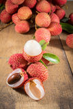 Lychee. Fresh lychees. Lychee with leaves on a wooden table Royalty Free Stock Images
