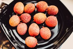 Lychee fruit on a black plate. View from above stock image