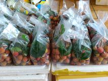 Lychee fruits packed with leaves, street Asian market Stock Photo