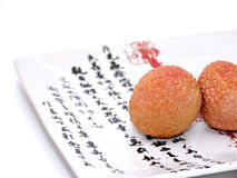 Lychee On a Japanese Plate. Two Lychee (litchi) placed on a white plate with Japanese (kanji) writing. Close Up Stock Image