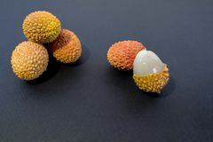Lychee Litchi with a stone and bright, bumpy skin on dark blue black background. stock images
