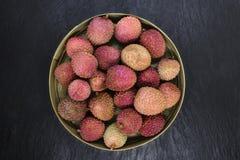 Lychees τα φρούτα στο στρογγυλό μπαμπού κυλούν στη μαύρη επιφάνεια υποβάθρου πετρών με το διάστημα αντιγράφων στοκ φωτογραφία με δικαίωμα ελεύθερης χρήσης