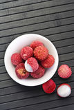 Lychees in bowl on black wood Stock Images