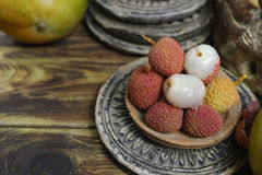 Lychees on wooden background - exotic and tropical fruit Royalty Free Stock Photo