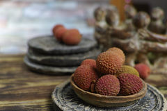 Lychees on wooden background - exotic and tropical fruit Stock Photos