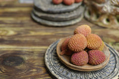 Lychees on wooden background - exotic and tropical fruit Royalty Free Stock Photos