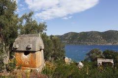 Lycian有地中海的样式石棺在背景中 免版税库存图片
