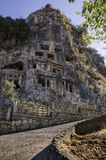 Lycian tombs in the rocks above Fethiye, Turkey. Fenced off by fences as monuments Royalty Free Stock Photo