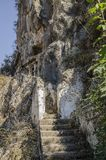 Lycian tombs in the rocks above Fethiye, Turkey, in the foreground the staircase leading to the graves. The slopes were covered with shrubs Stock Images