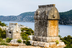 Lycian tombs in Simena on a hill above the sea. Royalty Free Stock Photos