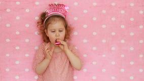 lyckönskan En söt liten flicka som blåser partihorn, leende, har gyckel, skrattar och firar lycklig födelsedag Närbild lager videofilmer