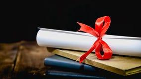 Lyckönskan för att avlägga examen akademikermössan och avläggandet av examen bläddrar, bundet med det röda bandet, på en bunt av  arkivfoton
