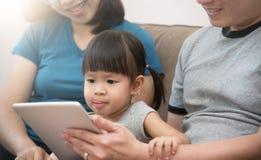 Lycka av den asiatiska familjen som sitter och spelar den digitala minnestavlan till Royaltyfria Foton