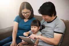 Lycka av den asiatiska familjen som sitter och spelar den digitala minnestavlan till royaltyfria bilder