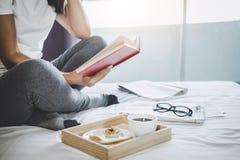 Lycka för ung kvinna på sovrum, i att tycka om läseböcker och n royaltyfri foto