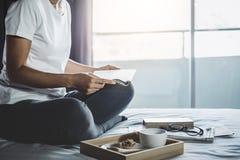 Lycka för ung kvinna på sovrum, i att tycka om läseböcker och tidningen i ferie med morgonkaffe, avkoppling och rekreation royaltyfri bild