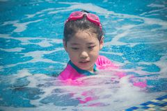 Lycka och att le den asiatiska gulliga lilla flickan har rolig k?nsla och tycker om i simbass?ng arkivfoton