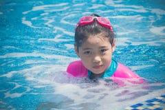 Lycka och att le den asiatiska gulliga lilla flickan har rolig k?nsla och tycker om i simbass?ng royaltyfri bild