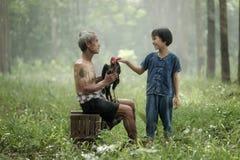 Lycka och harmoni i familjeliv lycklig begreppsfamilj Gammal fader som ler med hans dotter i gummiträdfältet Arkivfoton