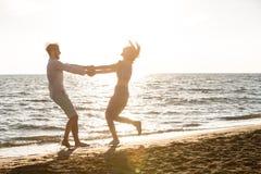 Lycka- och romantikerplatsen av förälskelsepar blir partner med på stranden royaltyfri fotografi