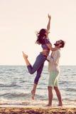 Lycka- och romantikerplatsen av förälskelsepar blir partner med på stranden royaltyfria bilder