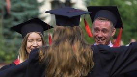 Lycka på framsidor av att avlägga examen studenter i den akademiska klänningen, krama för vänner arkivfilmer