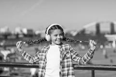 Lycka ?r f?r nu Lilla flickan lyssnar till utomhus- musik Lycklig barnkl?derh?rlurar Little musikventilator Lyckligt litet fotografering för bildbyråer