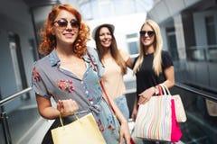 Lycka, v?nner, shopping och roliga begrepp-le unga kvinnor med shoppingp?sar royaltyfri fotografi