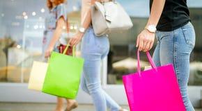 Lycka, v?nner, shopping och roliga begrepp-le unga kvinnor med shoppingp?sar royaltyfria bilder
