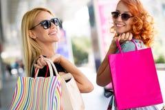 Lycka, v?nner, shopping och roliga begrepp-le unga kvinnor med shoppingp?sar arkivbilder