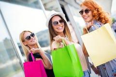 Lycka, v?nner, shopping och roliga begrepp-le unga kvinnor med shoppingp?sar fotografering för bildbyråer