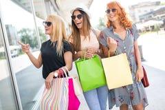 Lycka, v?nner, shopping och roliga begrepp-le unga kvinnor med shoppingp?sar royaltyfri bild