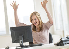 Lyckad affärskvinna With Arms Raised som ser datoren Arkivbild